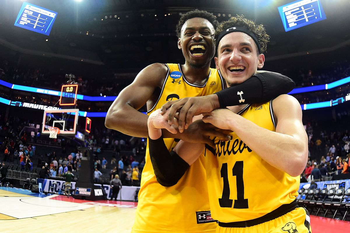 CHARLOTTE, NC - MARCH 16:  K.J. Maura #11 and teammate Jourdan Grant #5 of the UMBC Retrievers celebrate their 74-54 victory over the Virginia Cavaliers during the first round of the 2018 NCAA Men's Basketball Tournament at Spectrum Center on March 16, 2018 in Charlotte, North Carolina.  (Photo by Jared C. Tilton/Getty Images)