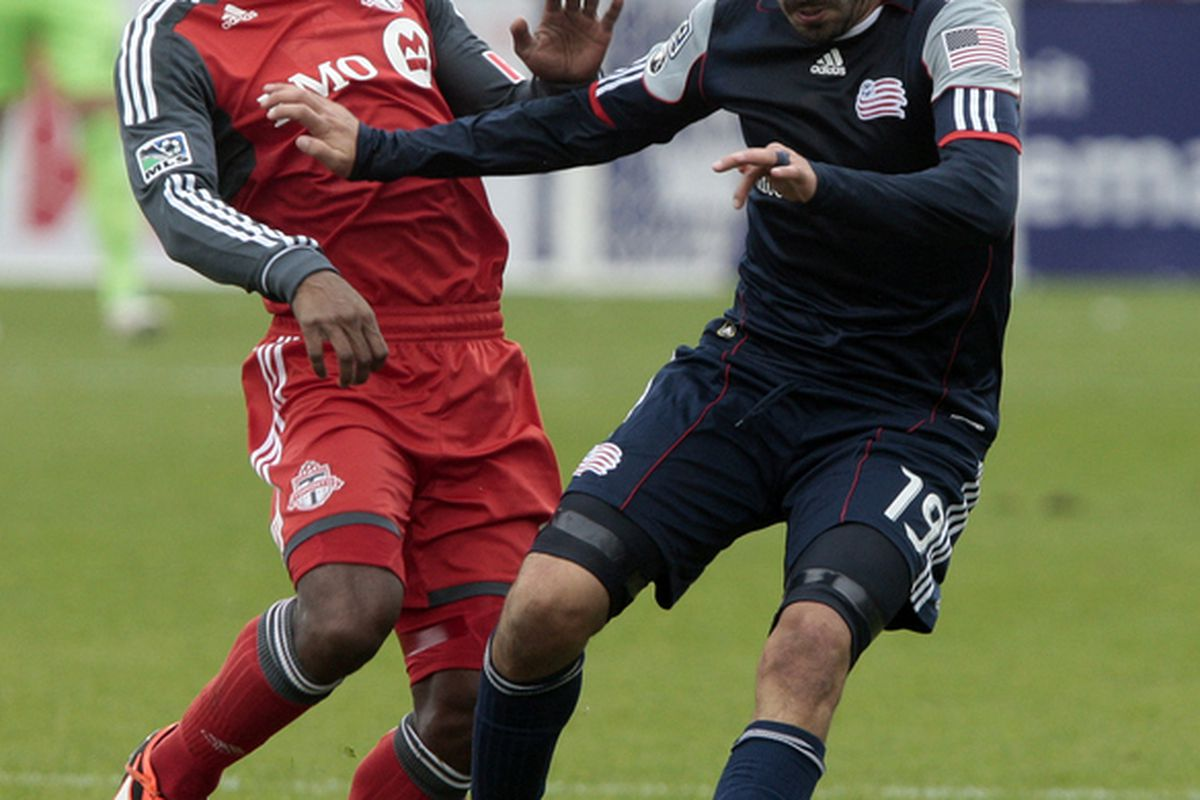 TORONTO, CANADA - OCTOBER 22: Ryan Johnson #9 of Toronto FC  is pushed by Monsef Zerka #19 of New England Revolution during MLS action at BMO Field October 22, 2011 in Toronto, Ontario, Canada. (Photo by Abelimages/Getty Images)