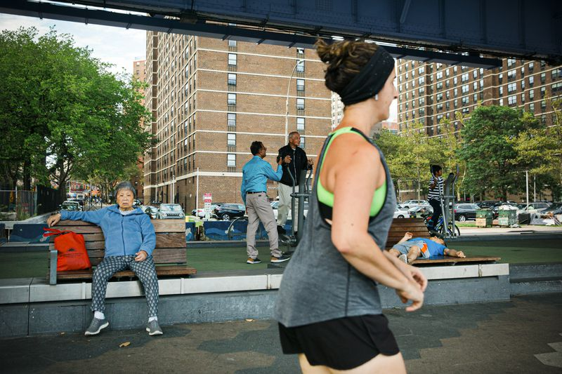 People exercising on South Street along the East River in New York's Two Bridges neighborhood.