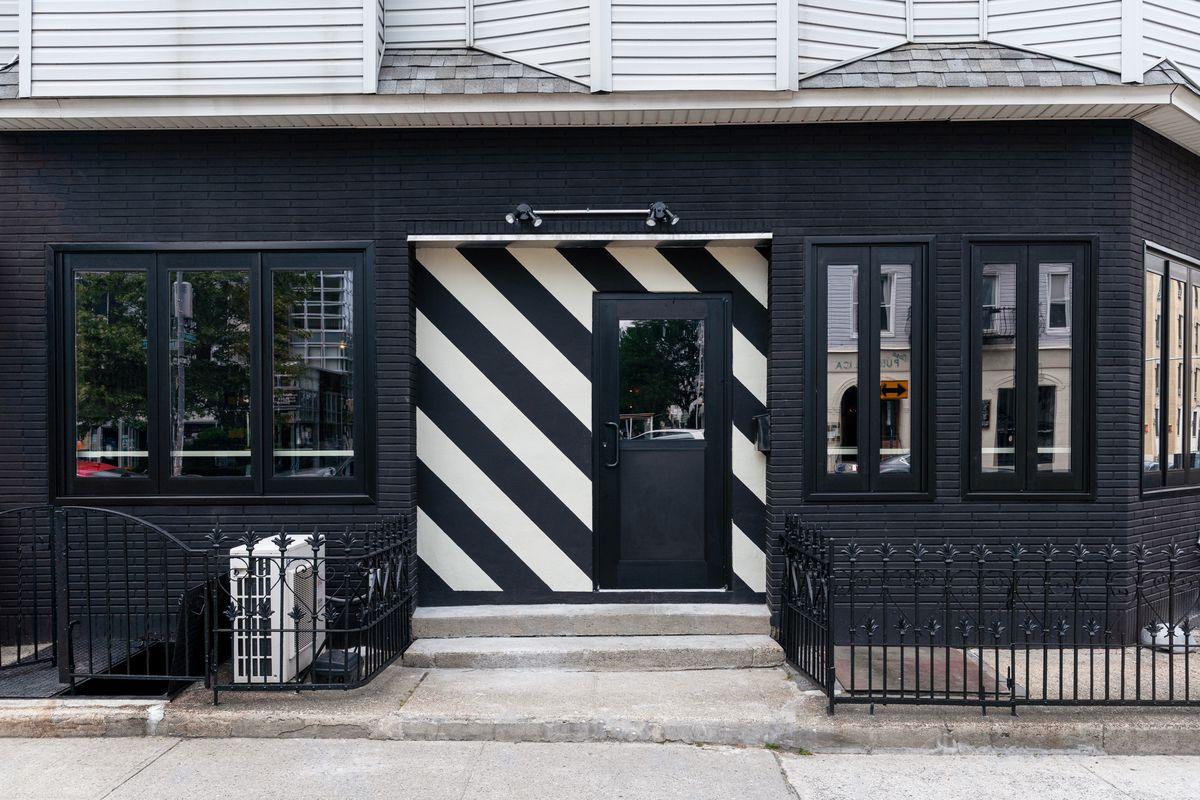 A black corner bar with a diagonal black-and-white entrance