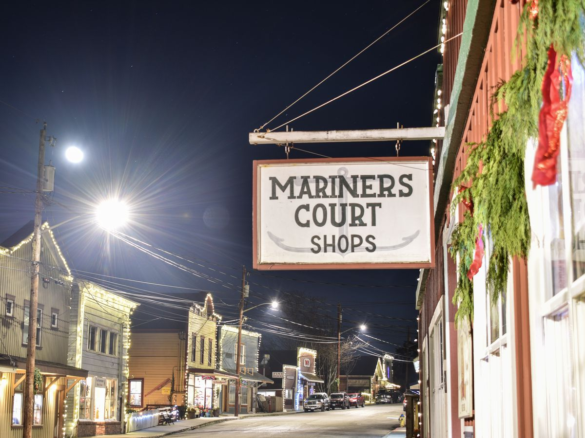 """At night, a street is lined on either side with old two-story buildings. A sign in the foreground says """"MARINERS COURT SHOPS."""""""