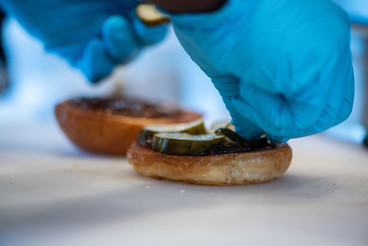 A hand in blue gloves lays down pickles on a bun inside a restaurant.