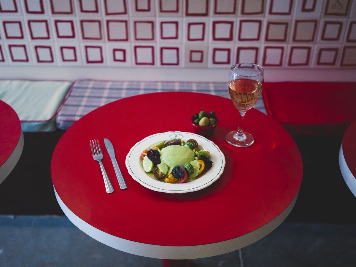 A plate of burrata, pesto, and vegetables sits in the middle of a red table with a glass of wine and a side dish filled with olives.