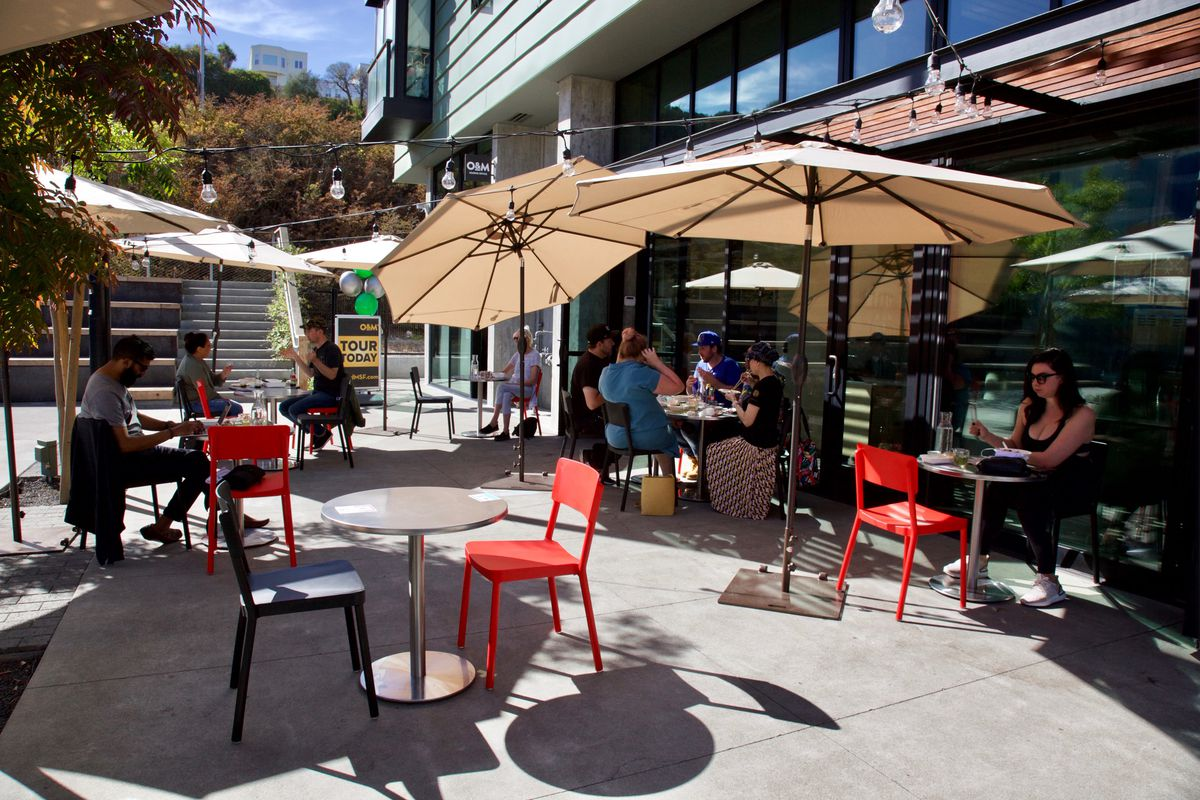 The patio dining setup in front of Kin Khao Dogpatch, with socially distanced tables set up under patio umbrellas