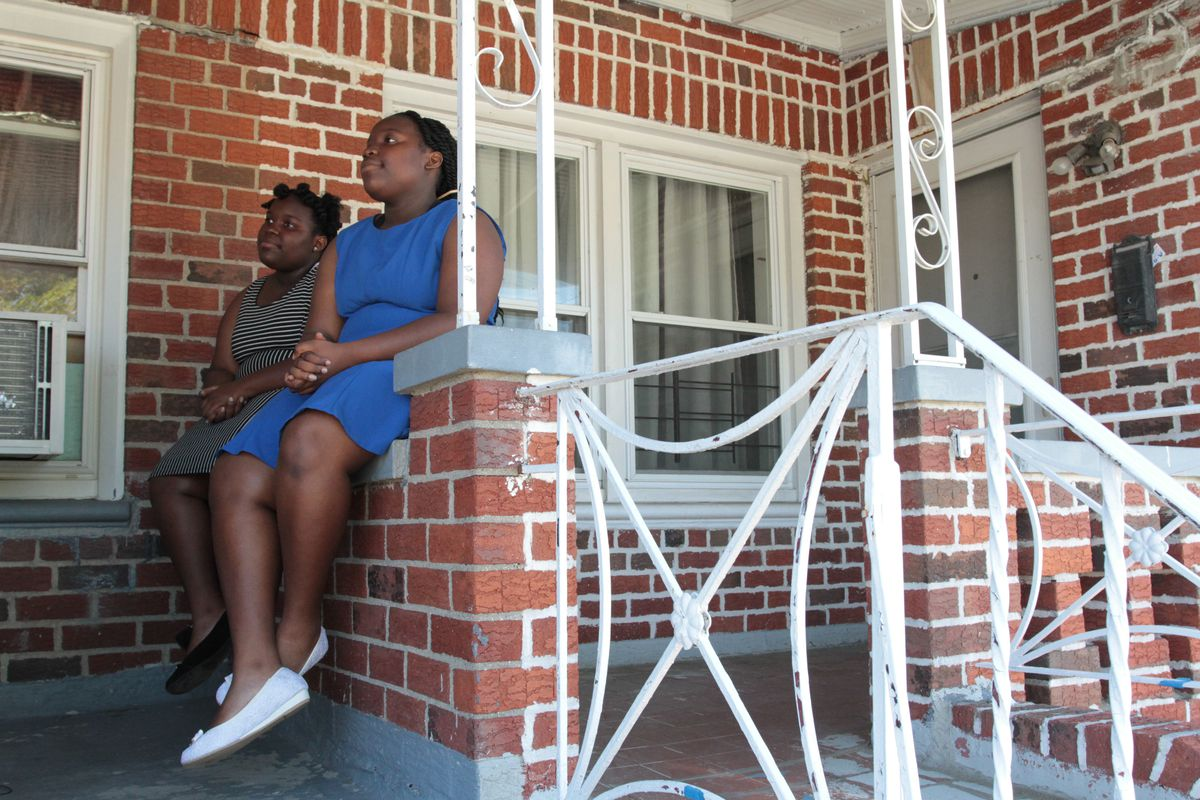 Elodie Oriental, 15, (left) and her twin sister, Ismaelle, sit outside their apartment in Canarsie, Brooklyn.