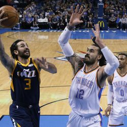 Utah Jazz guard Ricky Rubio (3) shoots in front of Oklahoma City Thunder center Steven Adams (12) in the first quarter of an NBA basketball game in Oklahoma City, Tuesday, Dec. 5, 2017. (AP Photo/Sue Ogrocki)