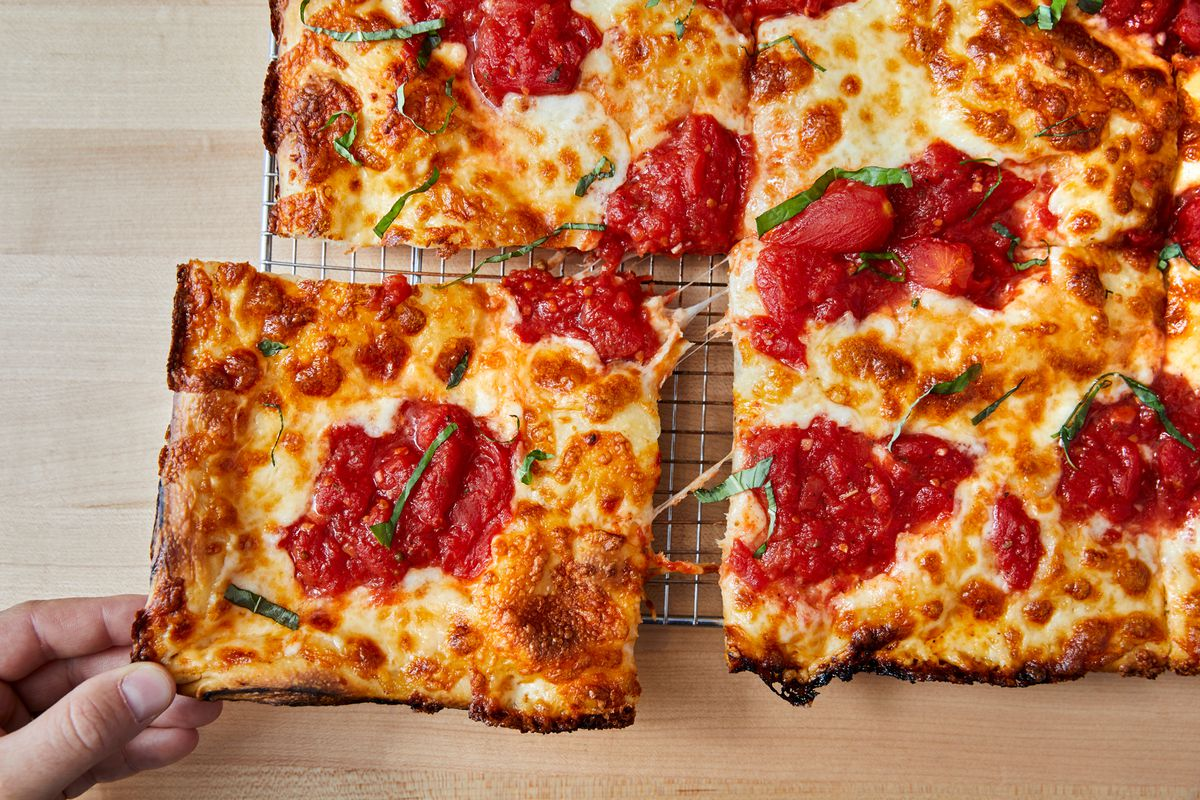 A square slice of pizza being pulled off from the corner.