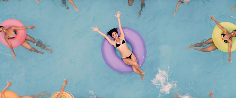 A woman in a bikini on an inner tube in a pool, surrounded by other swimmers in inner tubes.