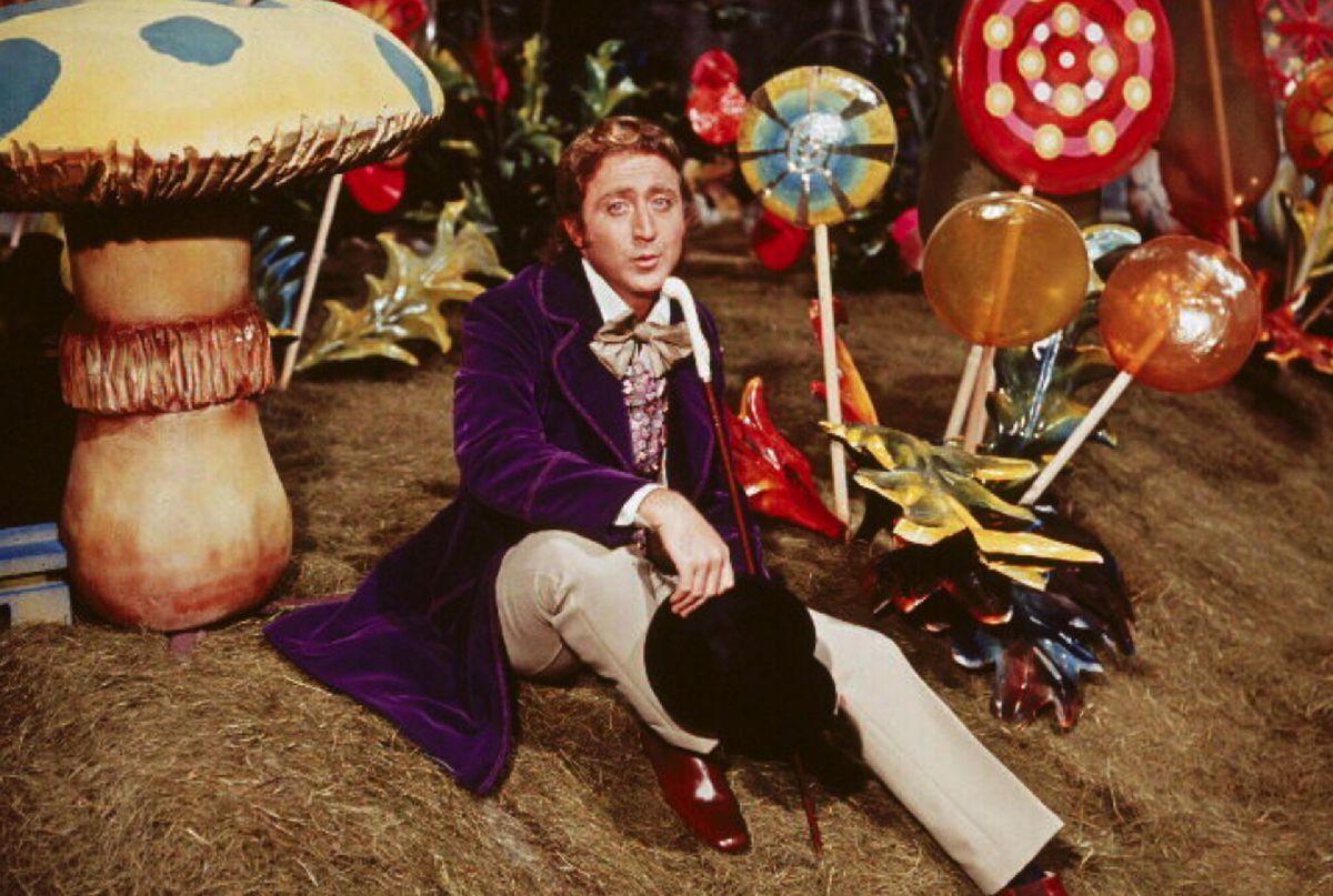 Gene Wilder as Willy Wonka, sitting amongst giant candies.