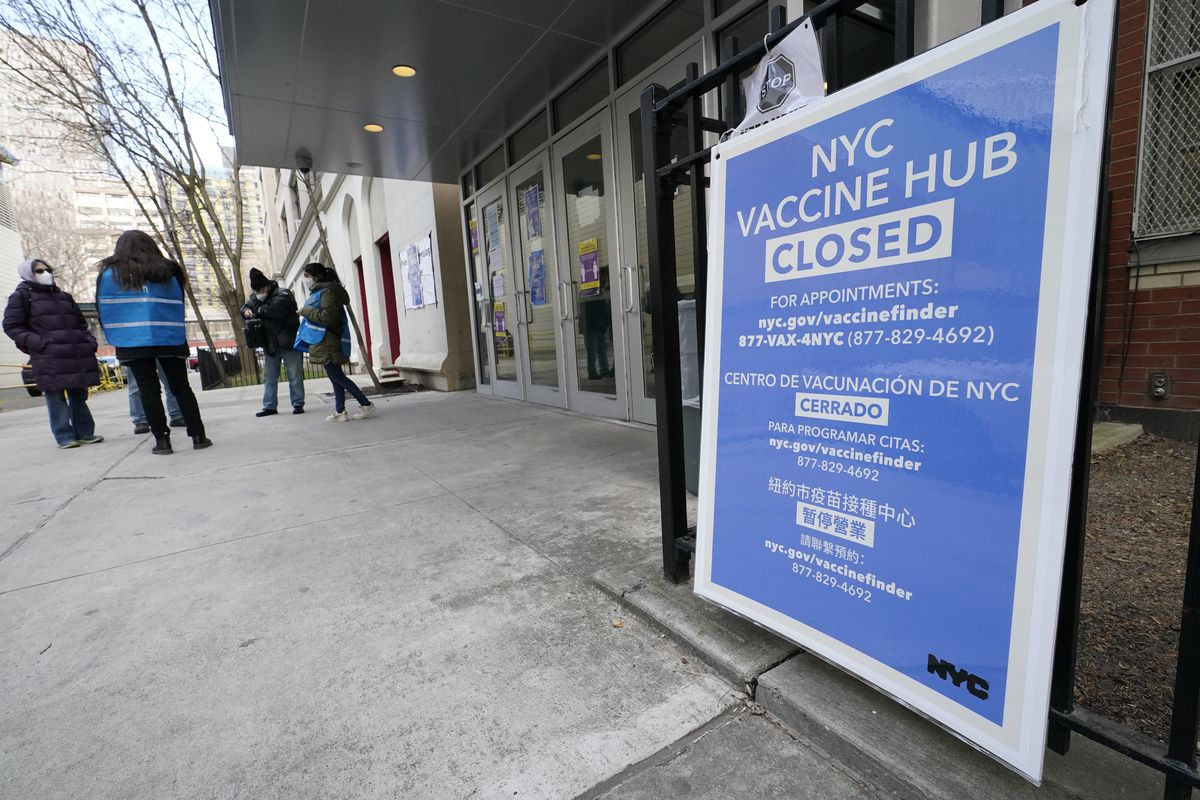 In this Jan. 21, 2021, file photo, people who had appointments to get COVID-19 vaccinations talk to New York City health care workers outside a closed vaccine hub in the Brooklyn borough of New York after they were told to come back in a week due to a shortage of vaccines.