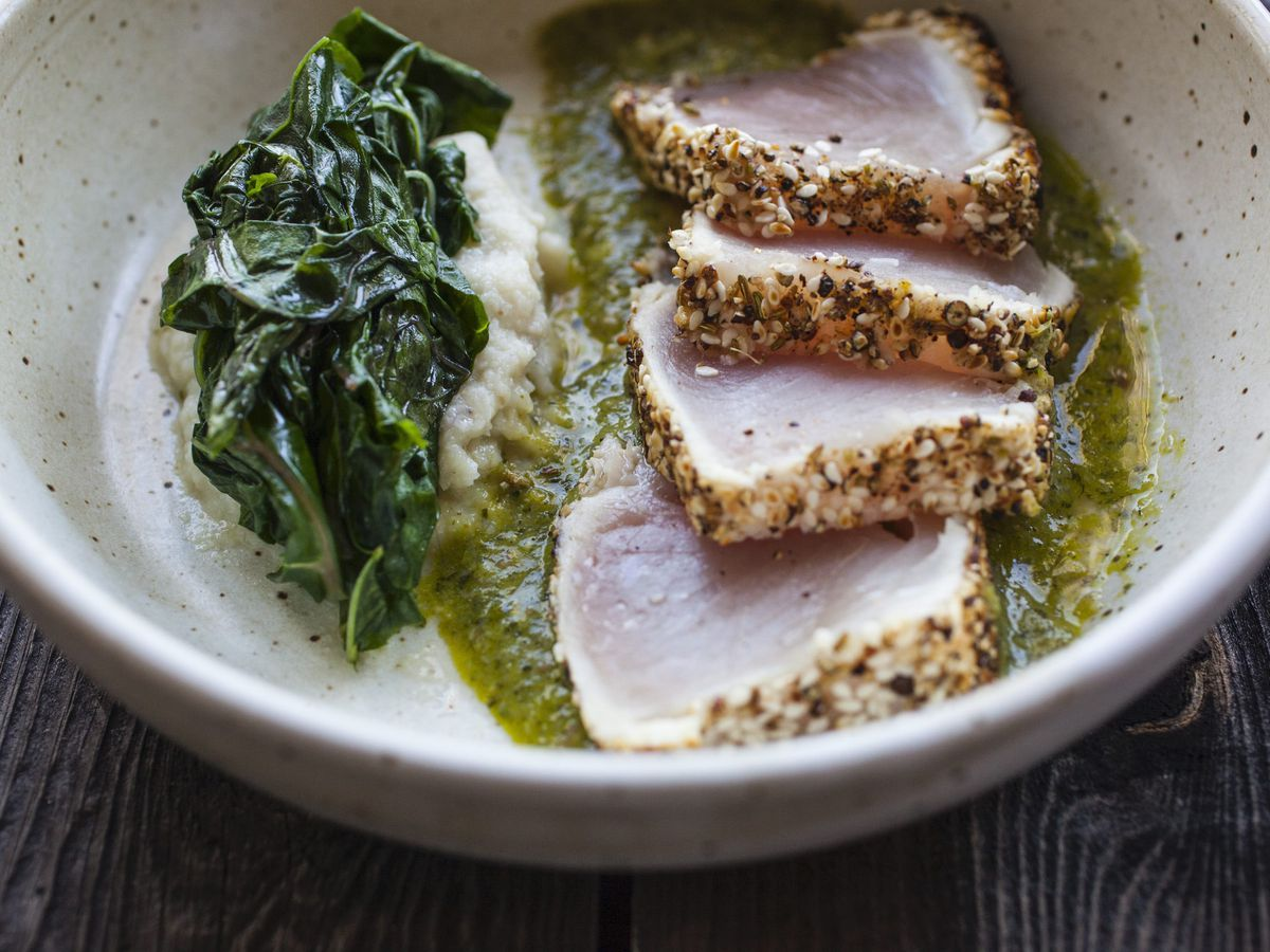 Slices of seared fish over a green puree in a bowl