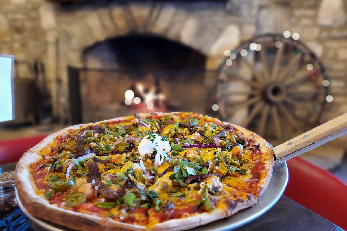 Pizza on a metal pan in front of a stone fireplace