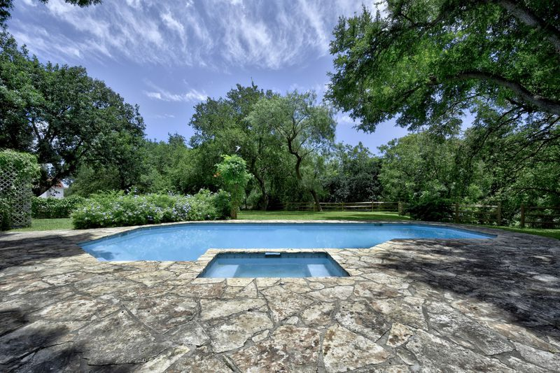 A pool and spa area has stone on the patio and lots of trees.