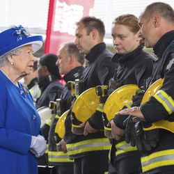Britain's Queen Elizabeth II, left, meets firefighters during a visit to the Westway Sports Centre which is providing temporary shelter for those who have been made homeless by the fire at Grenfell Tower,  in London,  Friday June 16, 2017. Relatives of those missing after a high-rise tower blaze in London are searching frantically for their loved ones, as the police commander in charge of the investigation says he hopes the death toll will not rise to three figures.
