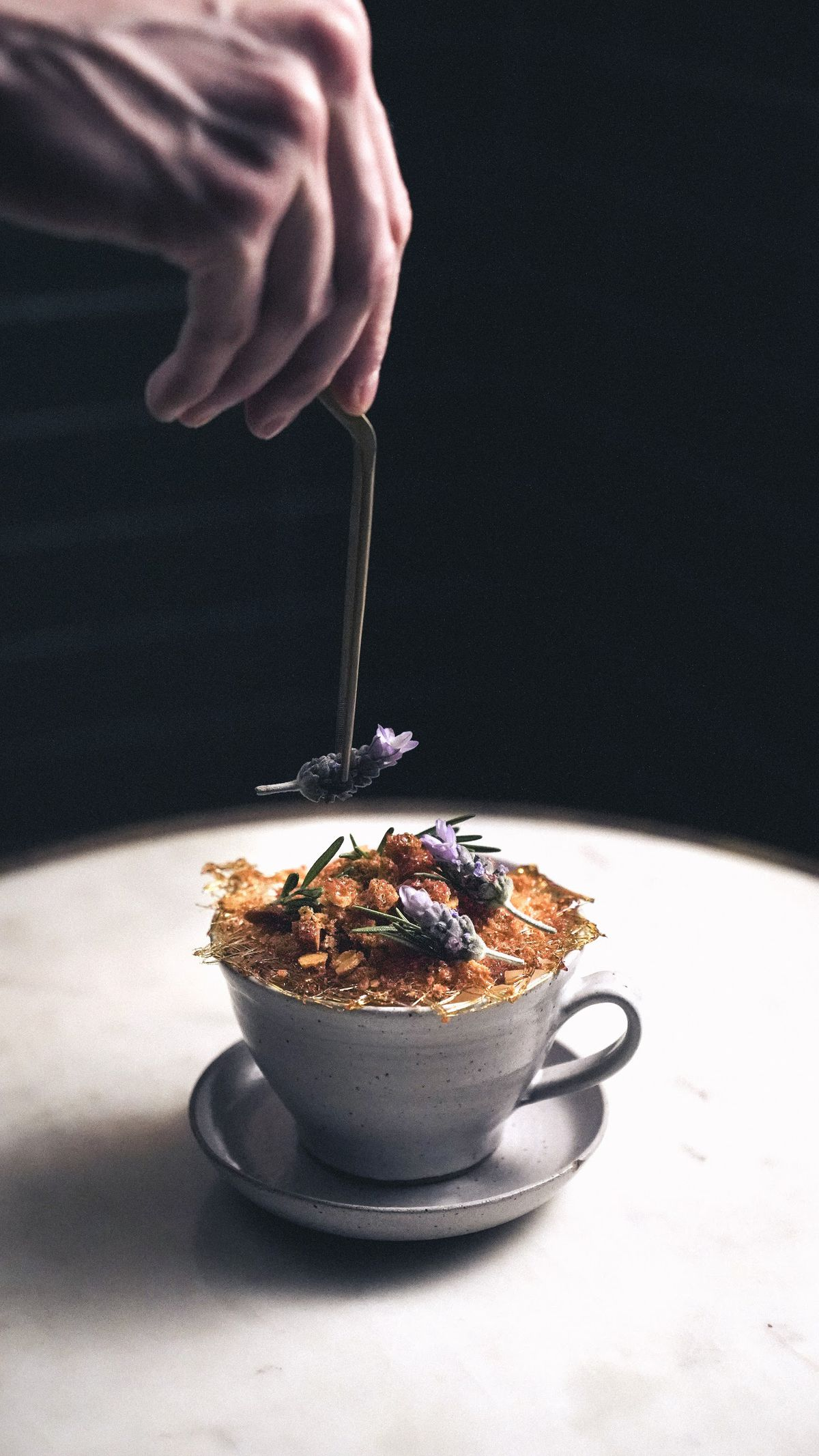 A latte is adorned with a layer of light brown crackling, while a hand off-screen uses tweezers to place a flower on top