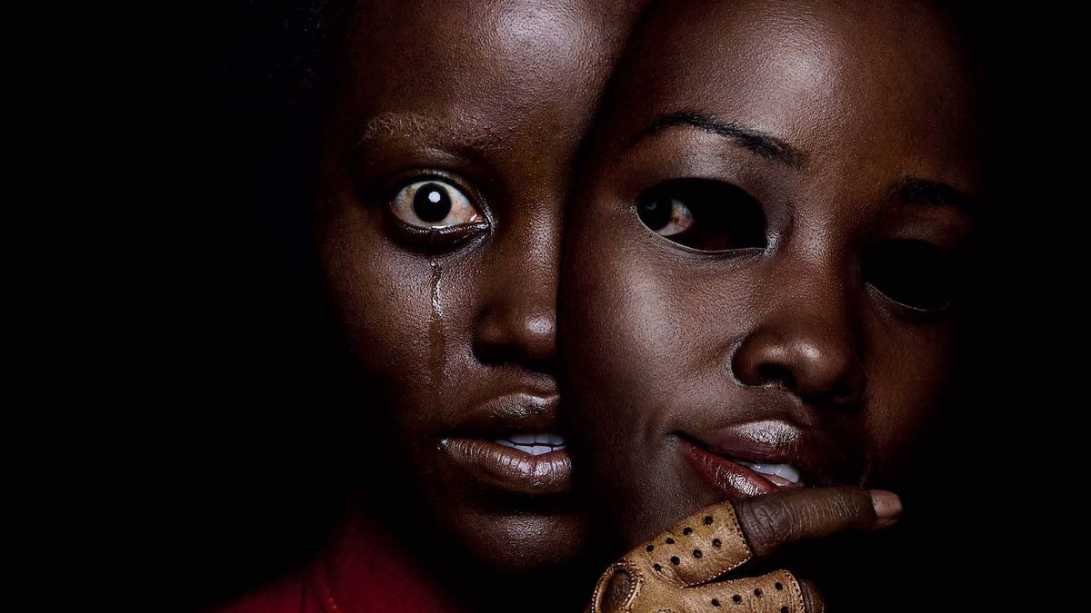 A wide-eyed black woman with a tear running down her face partially obscures her face with a mask that looks exactly like her face except that it's smiling.