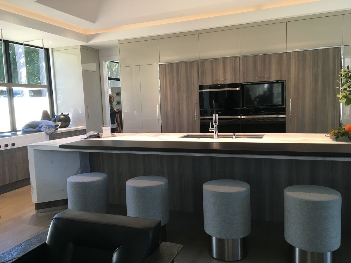 A huge modern kitchen with round barstools.