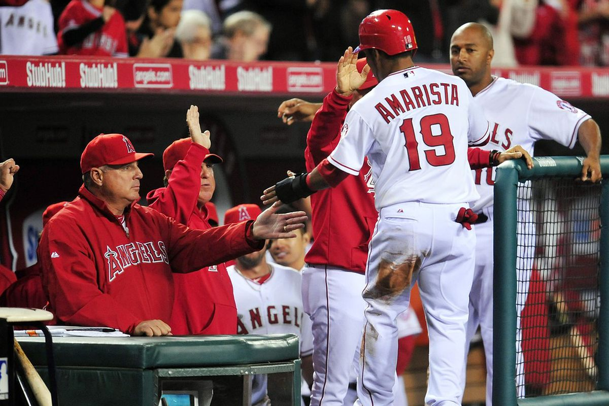 April 6, 2012; Anaheim, CA, USA; Los Angeles Angels second baseman Alexi Amarista (19) is congratulated after scoring in the eighth inning against the Kansas City Royals at Angel Stadium. Mandatory Credit: Gary A. Vasquez-US PRESSWIRE