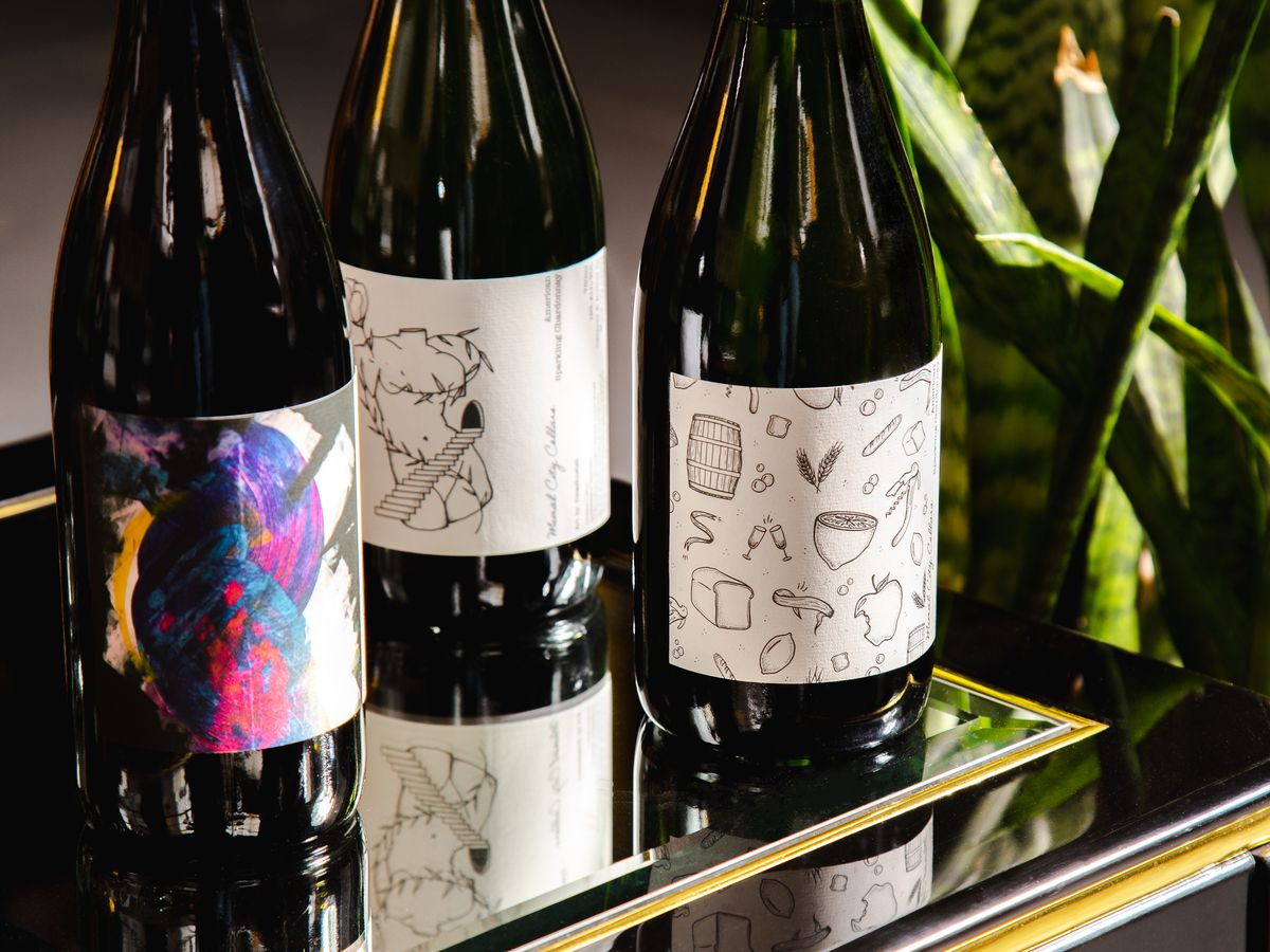 three bottles of wine with illustrations and visual art on the bottles