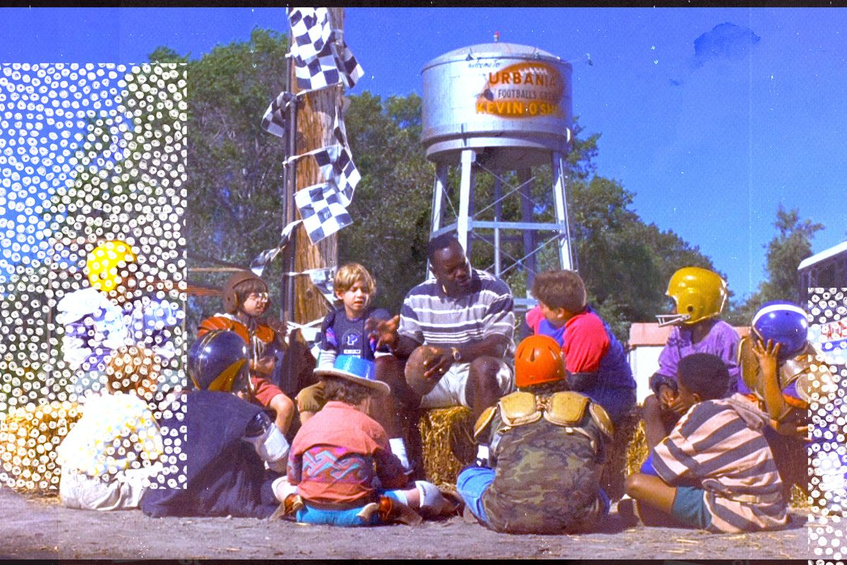 Cowboys great Emmitt Smith sits in a circle talking to kids in a scene from the movie Little Giants
