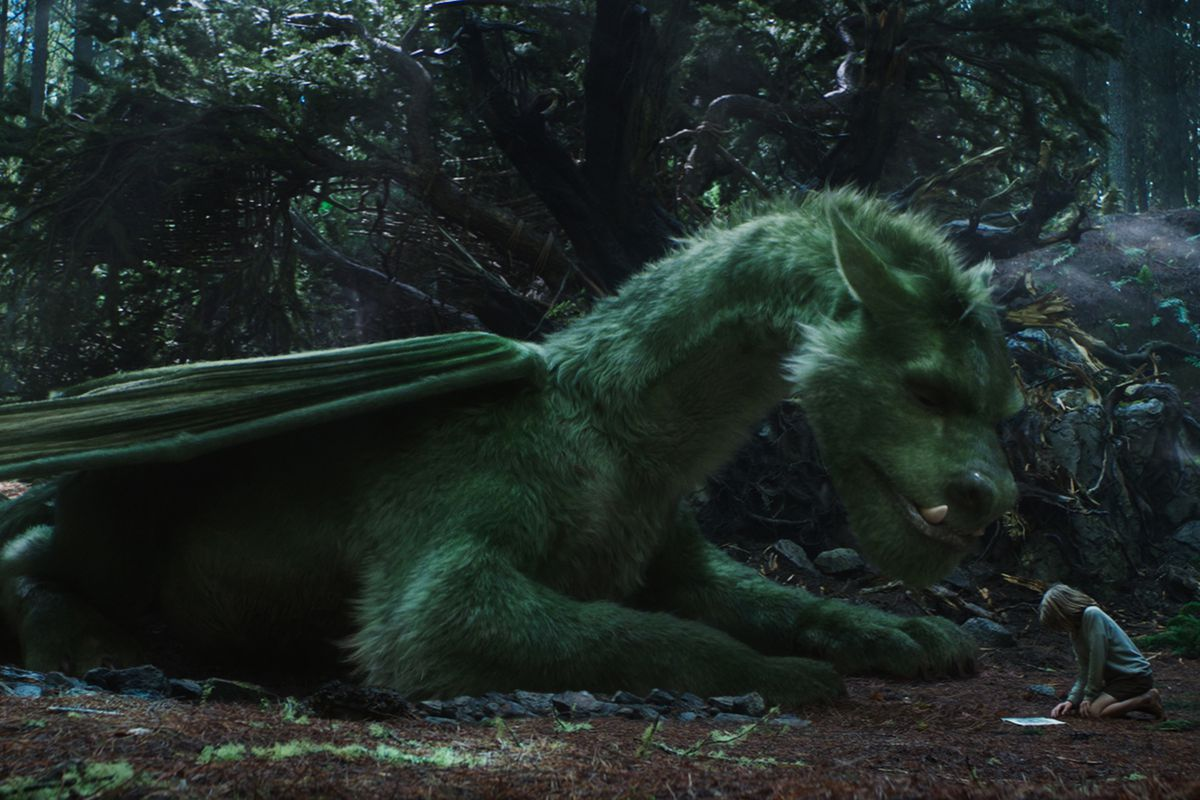the fluffy dog dragon from pete's dragon kneels next to his boy