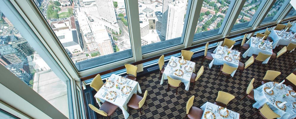An aerial view of a restaurant dining room with Boston skyline views