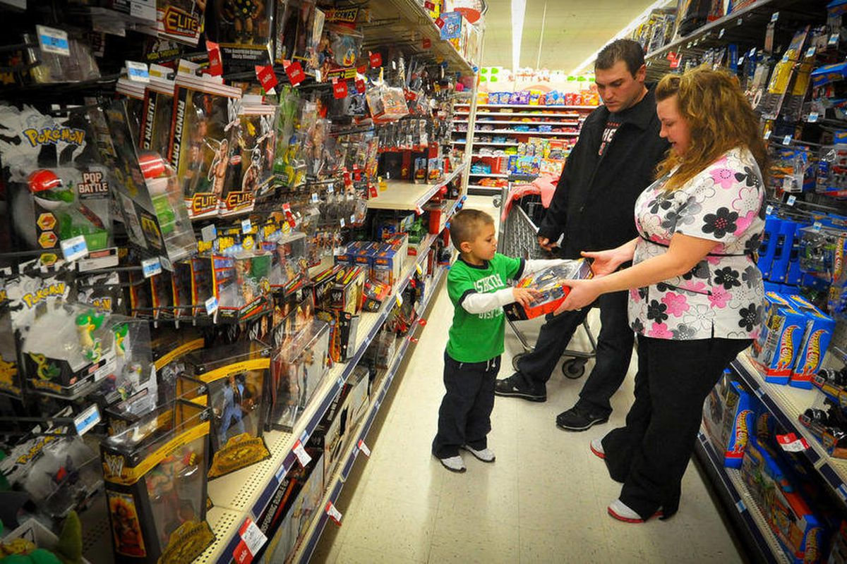 Kevin, center, Jolie, right, and Alex Lewis shop for a family they adopted for Christmas, Thursday Dec 15, 2011 at a Kmart in Omaha, Neb.  The Lewises had their layaway paid off at Kmart by an unknown good Samaritan. 'Layaway angels' are anonymously footi