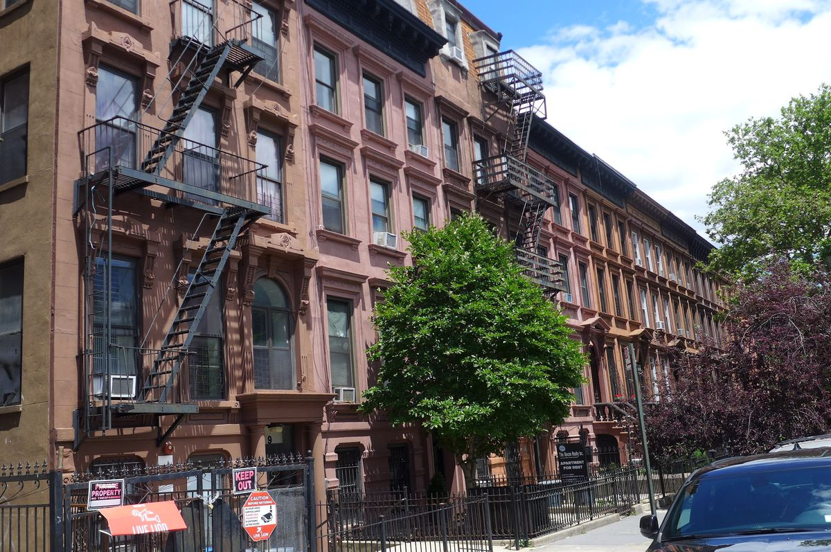 A row of sunny brownstones, with fluffy white clouds above.