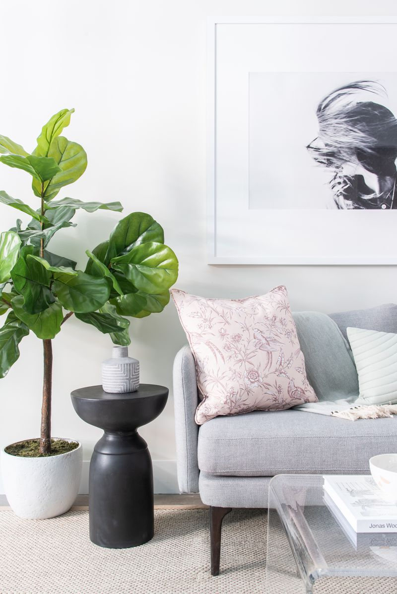 A living room with a grey couch, a planter, and a framed picture hanging on the wall.
