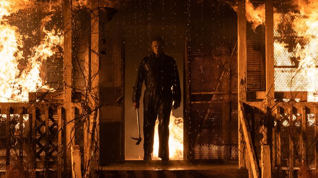 Michael Myers silhouetted against the doorway of a burning house in Halloween Kills