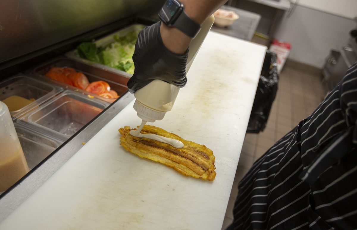 A person wearing black gloves squeezes mayo out of a squeeze bottle onto a flattened, fried plantain.