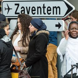 People stand near Brussels airport after being evacuated following  explosions that rocked the facility in Brussels, Belgium, Tuesday March 22, 2016. Authorities locked down the Belgian capital on Tuesday after explosions rocked the Brussels airport and subway system, killing  a number of people and injuring many more. Belgium raised its terror alert to its highest level, diverting arriving planes and trains and ordering people to stay where they were. Airports across Europe tightened security.