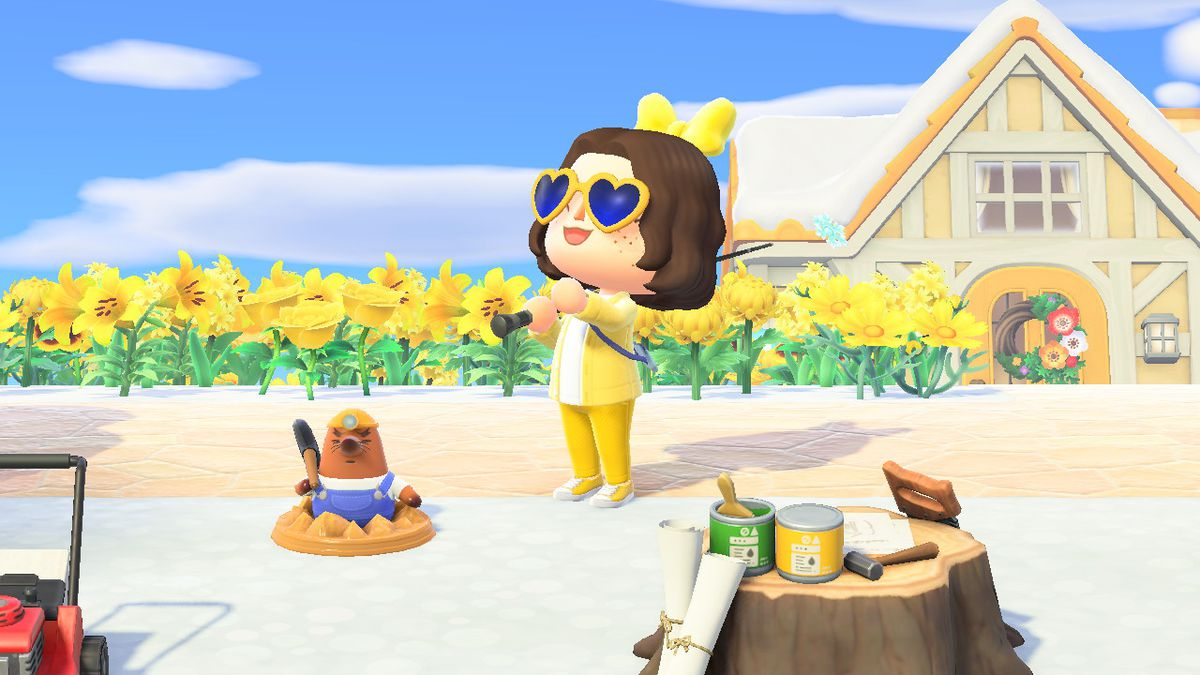 Animal Crossing character with brown hair wearing an all yellow outfit and holding a fishing pole, standing in front of a mole statue (Resetti)