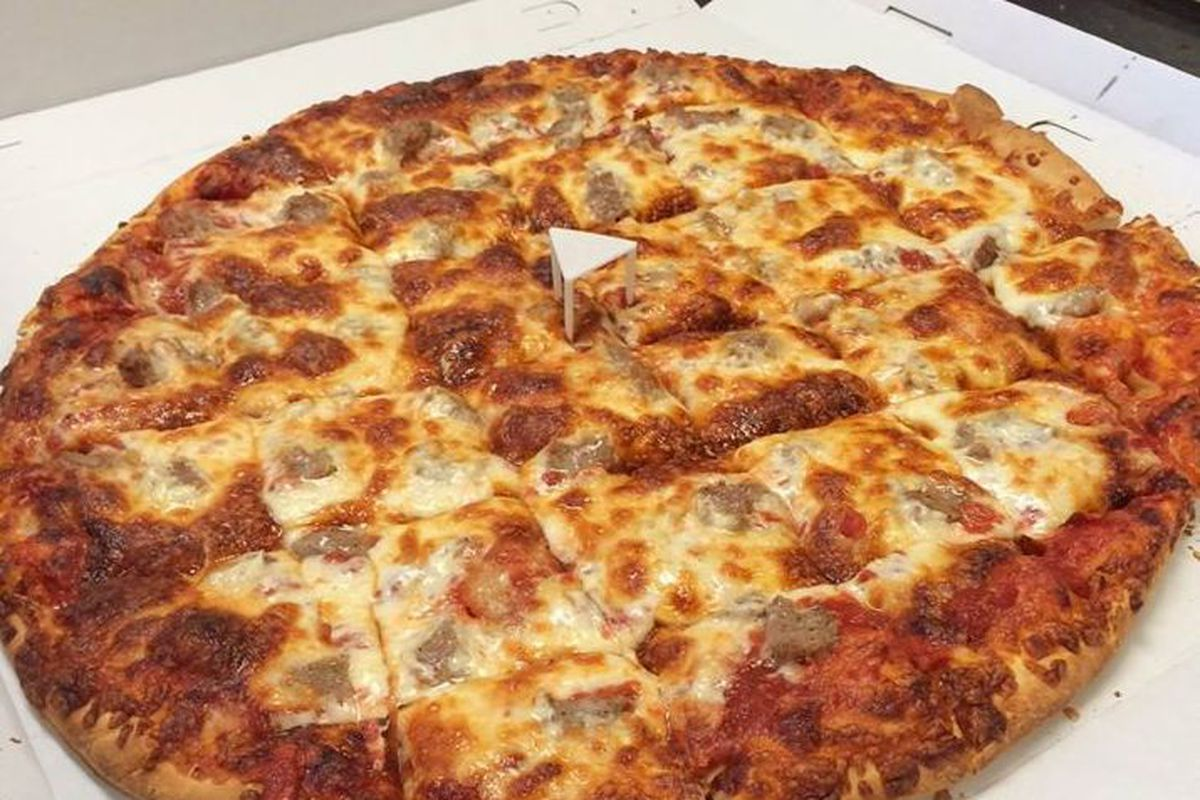 A pizza with lots of cheese cut into squares