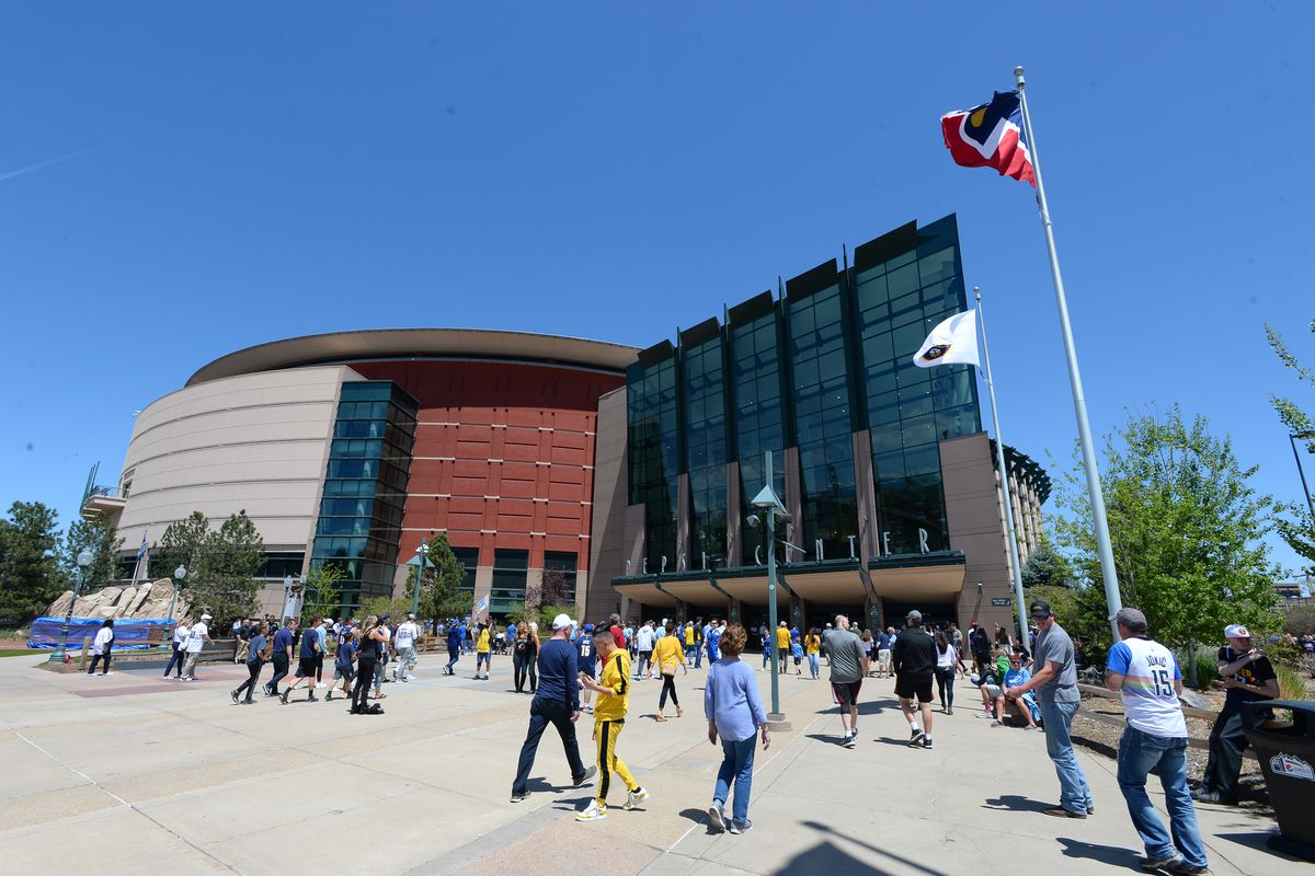 A photo of several of fans walking toward the main glass entry to the Pepsi Center