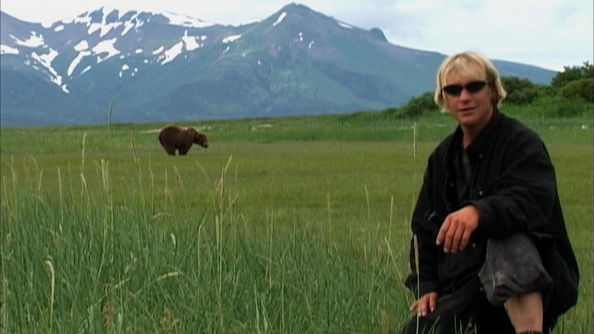 Timothy Treadwell poses in front of a grizzly bear