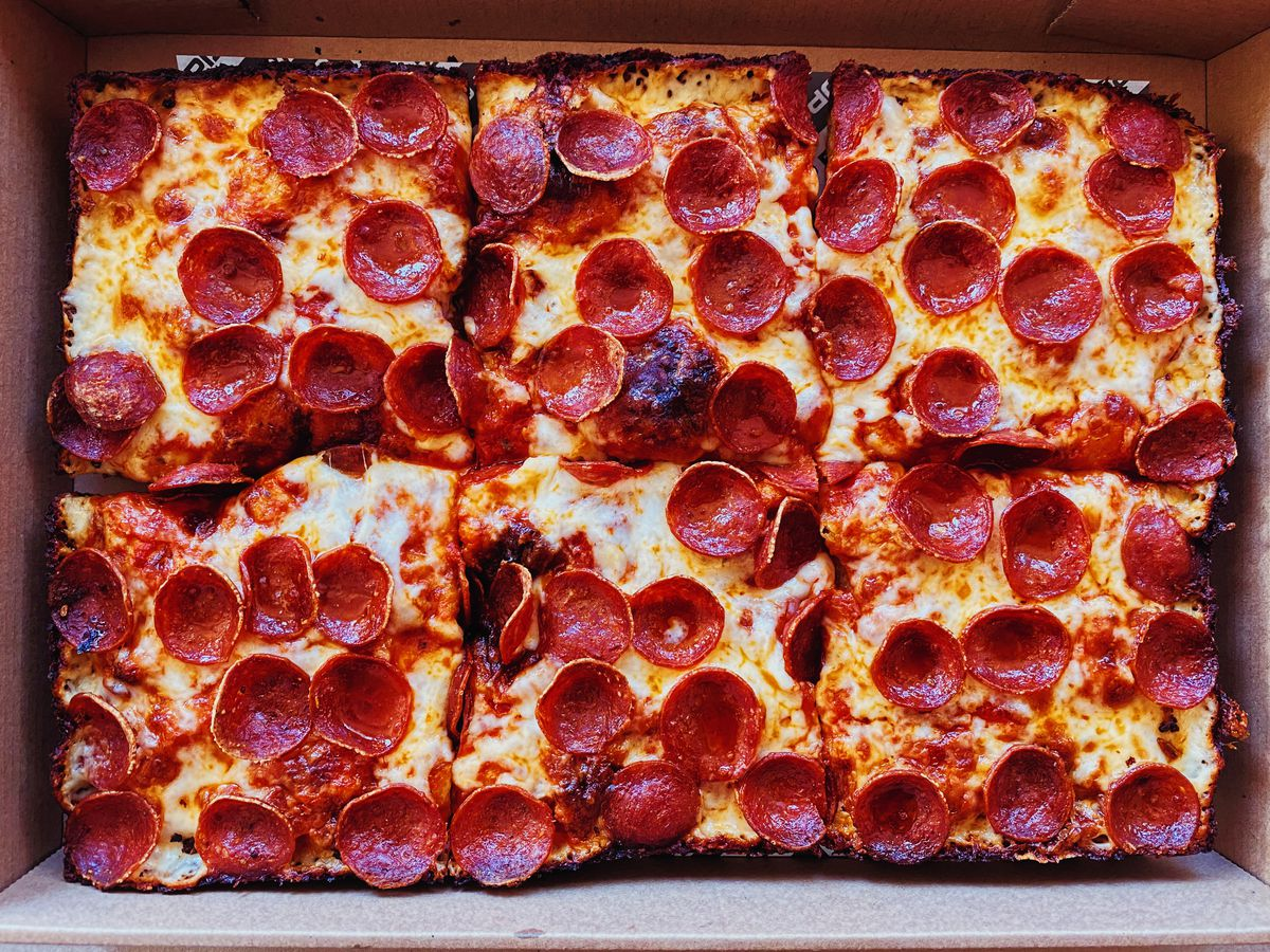 A rectangular pan pizza at Pop Pizza is covered in small, curly pepperoni