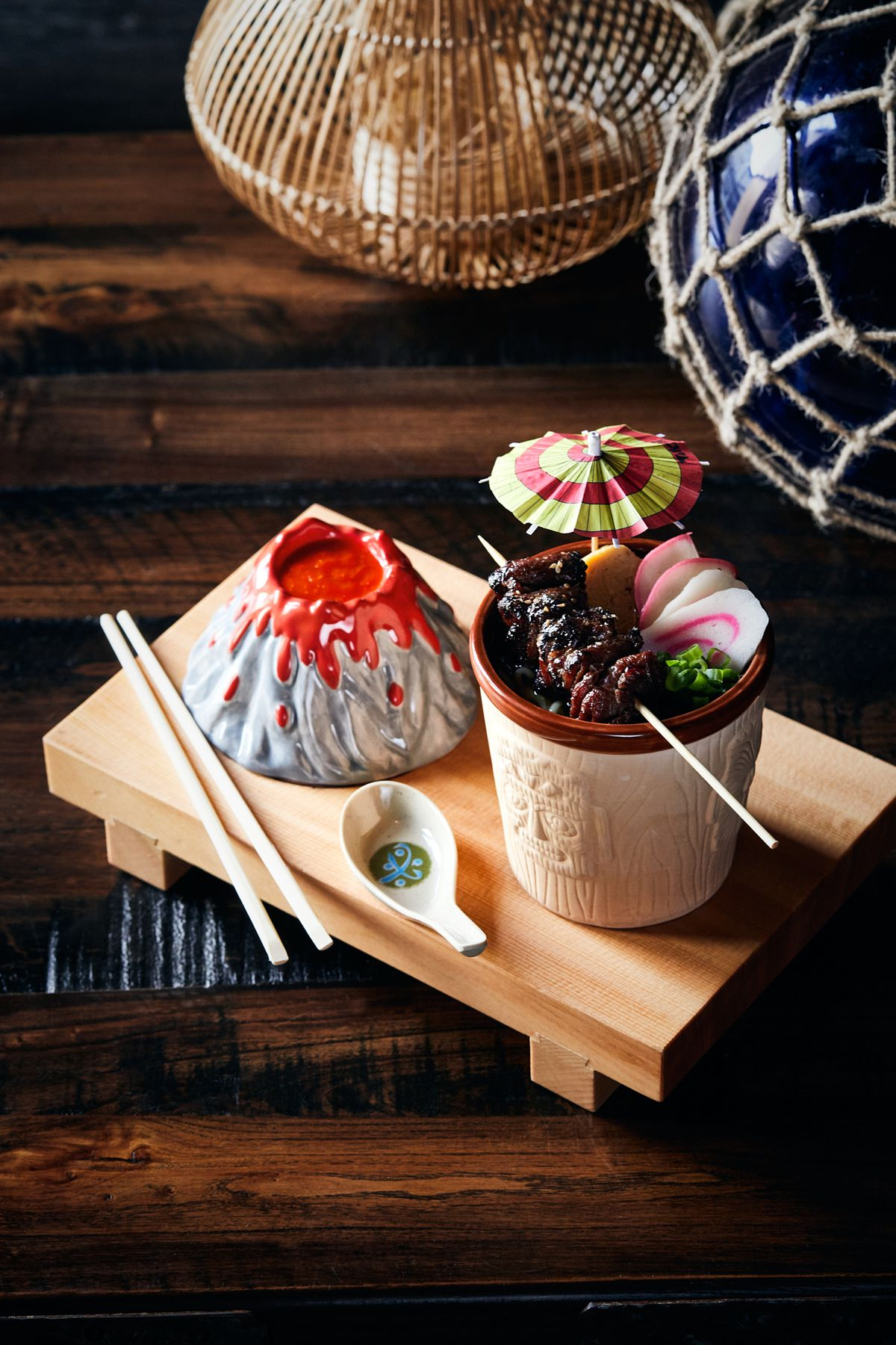 A wooden tray with a ceramic volcano replica and a mug with a skewer of meat