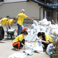 Donning yellow Mormon Helping Hands T-shirts, missionaries from the Sendai Japan Mission clean sludge from low income housing during missionary service project on June 16, 2011.