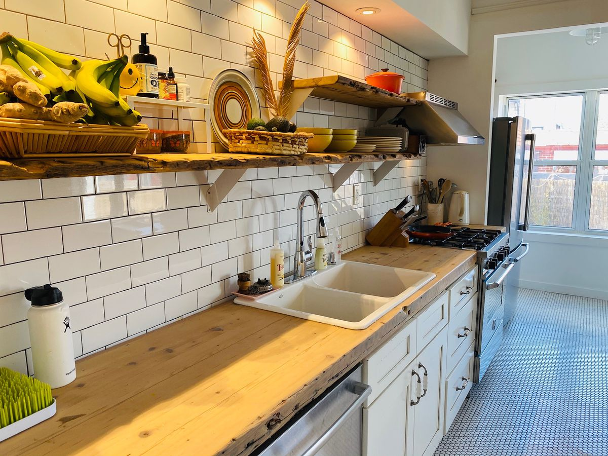 A kitchen with white wall tiles, wooden counters, and hexagon floor tiles.