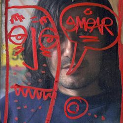 """In this photo taken on Monday, March 28, 2011, artist Cristian Gheorghiu is seen behind a """"Smear"""" character painted on a window frame at his East Hollywood garage studio in Los Angeles. Gheorghiu, known by his nickname of """"Smear,"""" faces an injunction that could bar him from profiting from art bearing his telltale graffiti """"tag."""" But Gheorghiu's lawyer says the city attorney's lawsuit is a thinly-veiled attempt around the First Amendment right to free expression."""