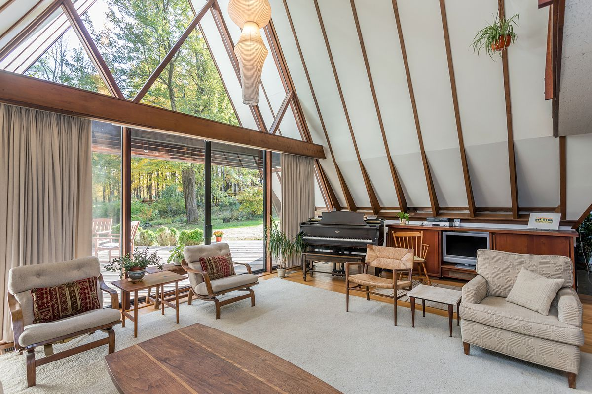 An A-frame's living room with one side of glass, soaring ceilings, and seating.