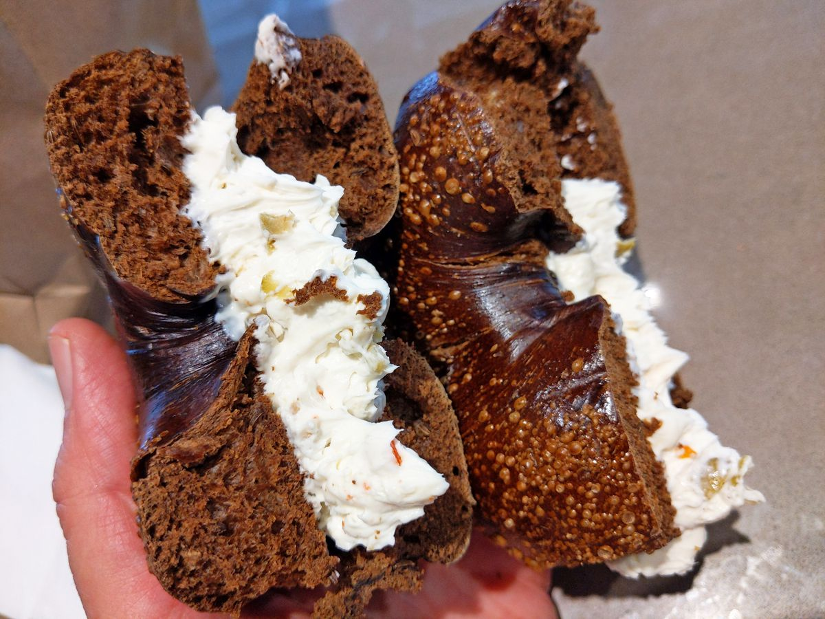 A very dark brown bagel cut in half and thickly spread with very white cream cheese flecked with olives.