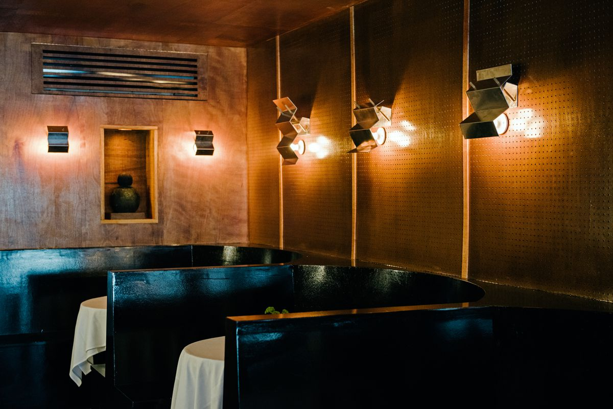 The interior of a dimly lit dining room, with two white tablecloth tables visible, dark banquettes, wooden walls, and overhead lights