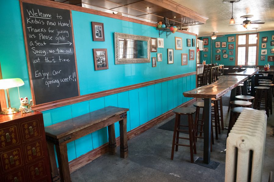 Kedai Mekan's bright blue dining room, with dark wood stools and tables.