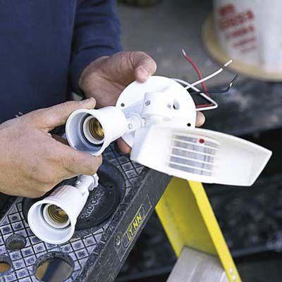 Man Assembles Outdoor Garage Floodlights