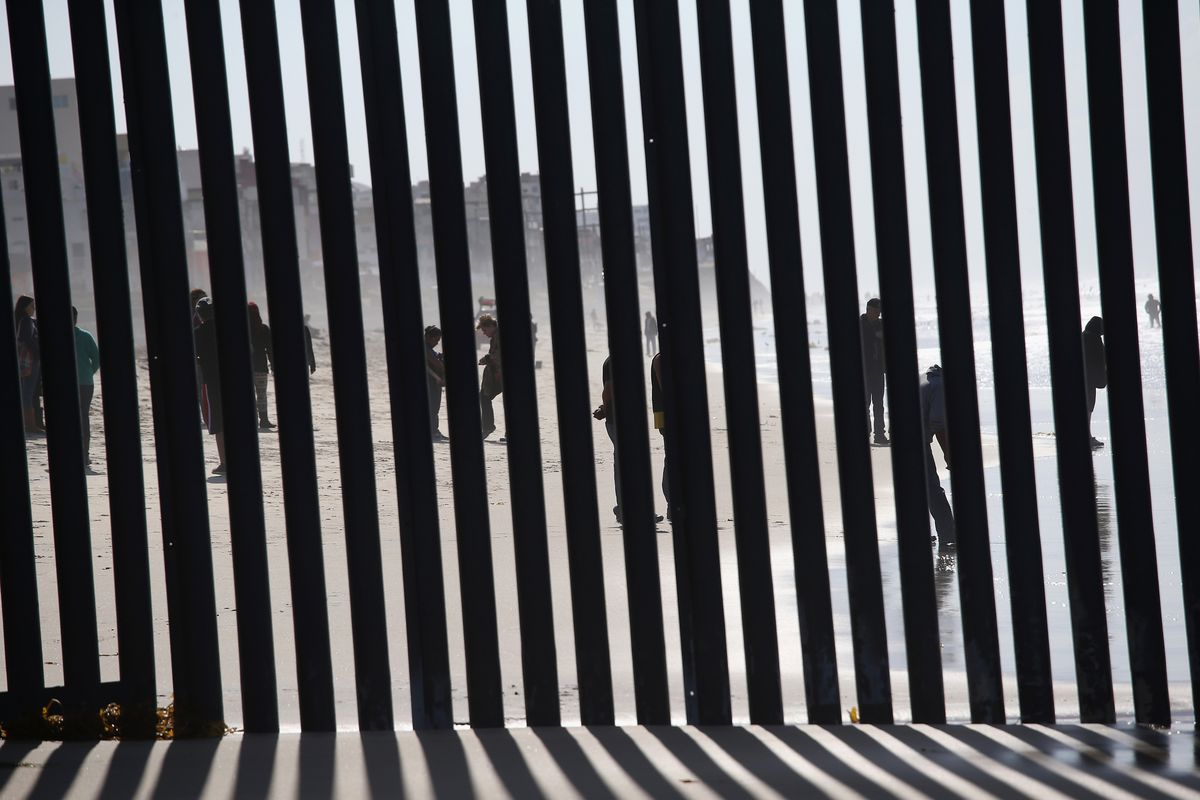 People viewed through the US/Mexico border fence in Tijuana.
