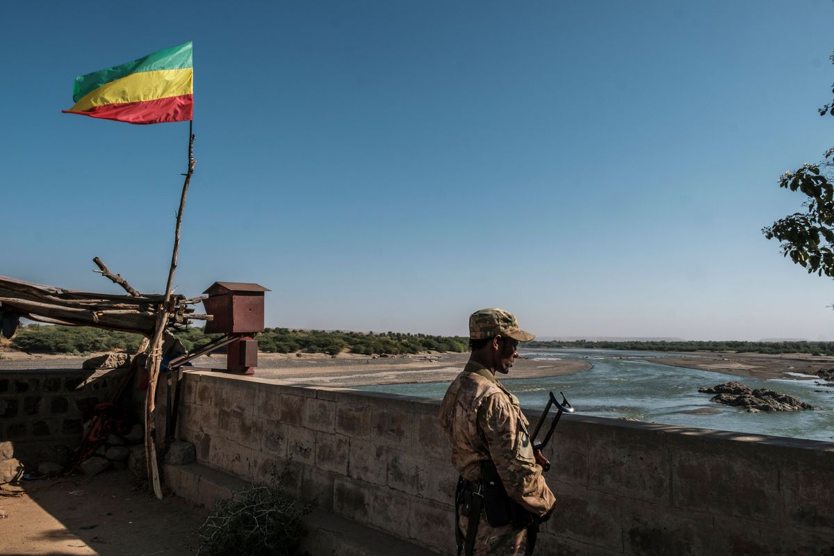 A soldier in fatigues and holding an assault rifle looks out over a stone wall. The flag, with (from top to bottom) horizontal green, yellow, and red stripes, flies atop a long stick, in a very blue sky.