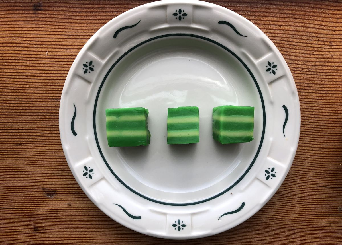 Green and yellow squares of steamed rice cakes are placed on white plate that is set on a wooden table