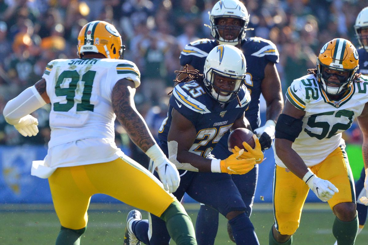 Los Angeles Chargers running back Melvin Gordon is defended by Green Bay Packers outside linebacker Preston Smith and linebacker Rashan Gary during the second quarter at Dignity Health Sports Park.